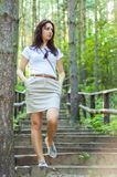 Girl walking through the forest pathway Stock Images