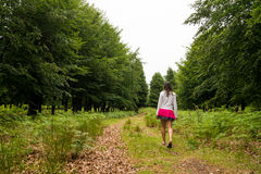 Girl walking in green forest Stock Image
