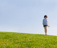 Girl walking on the green hill Stock Photos