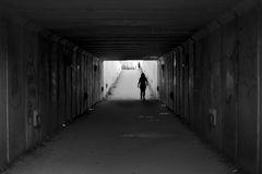 Girl walking on a grey urban pedestrian tunnel Royalty Free Stock Images