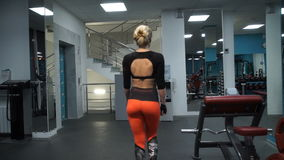 The girl is walking on the gym. Beautiful athletic girl goes to the simulators stock video footage