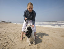Girl walking with her dog. (at the bach, blue sky Stock Photography