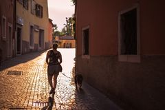 The girl is walking her dog on the street Stock Photos