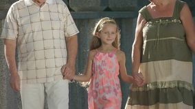 Girl walking with her grandparents. Child holding hands of grandparents in beautiful summer day, slow motion. Happy little girl stock video