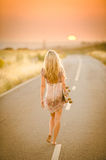 Girl walking with her skateboard. A barefoot blonde girl walking with her skateboard along a deserted road at sunset royalty free stock image