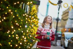 Girl walking with hot drink to go on a street of Paris decorated for Christmas stock photos