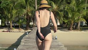 Girl walking on jetty and invites to follow her. Young caucasian woman in sunglasses swimsuit and straw hat happily walks on wooden jetty pier towards the beach stock footage