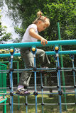 A girl walking on the ladder at the playground Stock Image