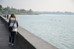 Girl walking on the lakeside Royalty Free Stock Image