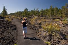 Girl Walking through Lava Rocks. Photo of a girl walking through lava rocks at the Lava Cast Forest, Newberry National Volcanic Monument, near Bend, Oregon, USA stock photos