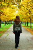 Girl walking through life. Girl walking on an alley autumn royalty free stock photography