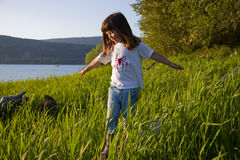 Girl Walking on a Log in Tall Grass. Girl balancing on a log in tall grass near the water, looking away. Horizontal Stock Image