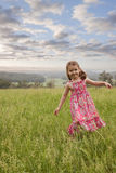 Girl walking in long grass. Happy young girl in long grass with rural landscape Stock Image