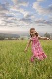 Girl walking in long grass Stock Image