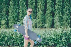 Girl walking with longboard in the park. Royalty Free Stock Photos