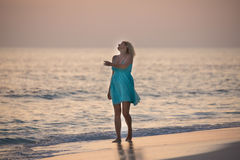 Girl is walking on the Maldivian beach and watching the sunrise Royalty Free Stock Photo