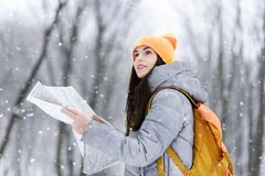 Girl Walking with the Map in the Forest. Brunette girl wearing grey jacket and yellow hat holding map and coners a lanscapes while walking with backpack in the royalty free stock images