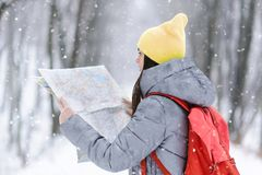 Girl Walking with the Map in the Winter Snowy Forest. Brunette girl wearing grey jacket and yellow hat coners a map while walking with backpack in the winter stock photography