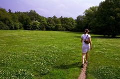 Girl walking through meadow royalty free stock photography
