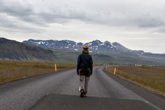 Girl walking in the middle of Icelandic road with. Royalty Free Stock Photos