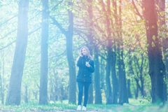 Talking on the phone, A girl is walking in the morning in a park with a smartphone and coffee, light toning Stock Images