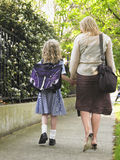 Girl Walking With Mother On Pavement Stock Photos