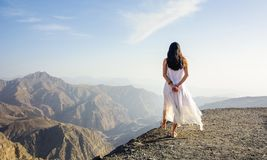Girl walking on the mountain edge. At sunset royalty free stock photo
