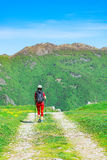 Girl walking on the mountain road. On the mountain road girl walks on a pilgrimage alone Royalty Free Stock Photos