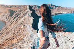 Girl walking on the mountain top. Over blue sea view. Follow me - POV Stock Image