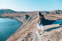 Girl walking on the mountain top. Over blue sea view stock photography