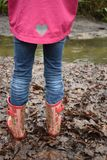 Girl walking in muddy boots stock photo
