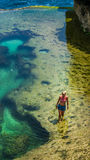 Girl walking in Natural Yellow Pool in Beautiful Cliff Formation, Bizarre Place, Nusa Penida Bali Indonesia Royalty Free Stock Photography