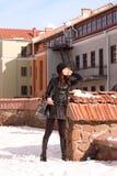 Girl walking near old buildings in winter. Beautiful girl with handbag walking near old buildings in winter Stock Photos