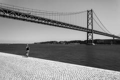 Girl walking near the Vasco Da Gama bridge. Black and white pic showing a girl taking a walk near the Vasco Da Gama bridge in Lisbona, Portugal royalty free stock photography