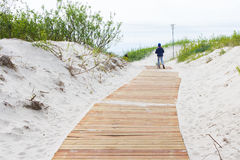 Girl walking on new light brown planks boardwalk in white sand d. Unes of Baltic sea Royalty Free Stock Image