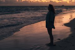 Girl walking on the ocean coast in morning Royalty Free Stock Photo