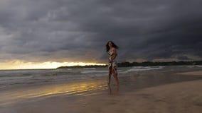 Girl walking on the ocean shore stock footage