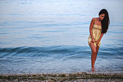 Girl walking out of the water lifting her dress up Stock Images