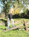 Girl walking over wooden swing Royalty Free Stock Image