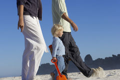 Girl (2-4) walking with parents on sandy beach, profile, low section, surface level Royalty Free Stock Photo