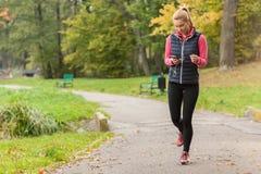 Girl walking in park with headphones Stock Image