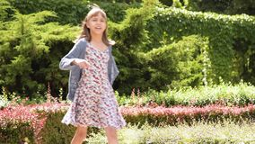 Girl walking at park. Little beautiful girl walking at park with sunlight reflecting off her hair stock footage