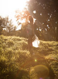 Girl walking in park in sun rays Royalty Free Stock Photo
