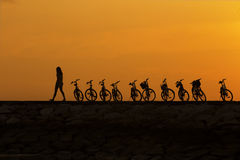 Girl walking past bike at jetty during sunrise Stock Photos