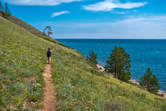 Girl walking on path along the shore of Lake Baikal Stock Image