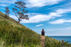 Girl walking on path along the shore of Lake Baikal Royalty Free Stock Photo