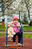 Girl walking on playground with toy dog Royalty Free Stock Photography