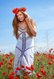 Girl walking in poppy field. Side view of girl walking in poppy field Stock Images