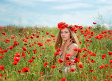 Girl walking in poppy field. Side view of girl walking in poppy field Royalty Free Stock Photos