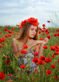 Girl walking in poppy field. Side view of girl walking in poppy field Royalty Free Stock Image